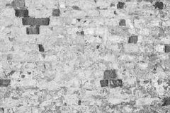 一个古老大厦的老墙壁的灰色纹理与一块被破坏的膏药层数和破裂的砖的 免版税库存图片