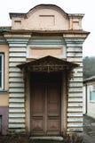 一个古老欧洲门面 在葡萄酒样式的门廊与一个小屋顶和一个木老门 图库摄影