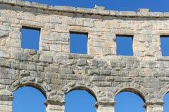一个古老罗马圆形剧场的墙壁有被成拱形的窗口的反对蓝天 免版税图库摄影