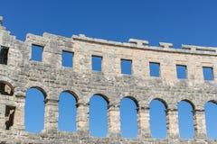 一个古老罗马圆形剧场的墙壁有被成拱形的窗口的在蓝天的背景 库存图片