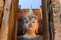 一个古老菩萨雕象的看法通过对寺庙Wat Si密友的门在Sukhothai历史公园 库存照片
