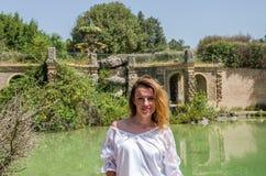 一个古色古香的喷泉的背景的年轻美丽的女孩,当走在公园在别墅多利亚Pamphili在罗马,意大利时 免版税库存图片