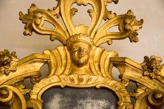 一个古色古香的镜子的一个被雕刻的框架的细节 免版税库存图片