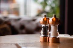一个古铜色盐和胡椒罐和研磨机坐在爱尔兰餐馆里面的一张桌 库存图片