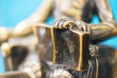 一个古铜色雕象的手的特写镜头拿着一本开放书的 雕塑特写镜头 棋 库存照片