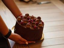 一个可口巧克力蛋糕用莓和黑醋栗在妇女` s手上在木背景 图库摄影