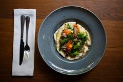 一个可口盘的一张顶视图在一块蓝色板材的在黑暗的木桌背景的一套餐具旁边 复制空间 图库摄影