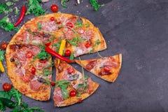 一个可口薄饼的顶视图与许多的肉、蕃茄和乳酪在灰色石背景 复制空间 库存照片