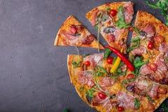 一个可口薄饼的顶视图与许多的肉、蕃茄和乳酪在灰色石背景 复制空间 免版税库存照片