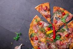 一个可口薄饼的顶视图与许多的肉、蕃茄和乳酪在灰色石背景 复制空间 库存图片