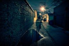 一个可怕人的阴影一个黑暗的都市城市胡同的在晚上 库存照片