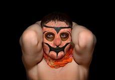 一个可怕的面具的人用在头后的手 免版税库存照片