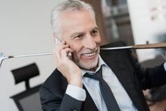 一个可敬的人在电话坐在桌边缘在他的办公室并且谈话 免版税库存图片