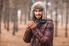 一个可爱的人温暖他的拿着一个热杯子的手 在秋天森林里 库存照片