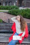 一个可爱的女孩在都市背景坐长凳并且写她想法在一个红色笔记本 她穿一件白色毛线衣, b 图库摄影