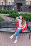 一个可爱的女孩在都市背景坐长凳并且写她想法在一个红色笔记本 她穿一件白色毛线衣, b 免版税库存照片