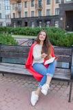 一个可爱的女孩在都市背景坐长凳并且写她想法在一个红色笔记本 她穿一件白色毛线衣, b 免版税图库摄影