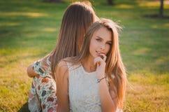 一个可爱的女孩的画象在一个夏天公园,在她后坐另一名妇女 免版税库存图片
