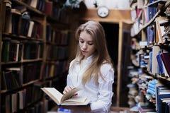 一个可爱的学生女孩的生活方式画象在葡萄酒图书馆或书店里 库存照片