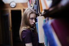 一个可爱的学生女孩的生活方式画象在葡萄酒图书馆或书店里 免版税库存照片