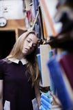 一个可爱的学生女孩的生活方式画象在葡萄酒图书馆或书店里 免版税图库摄影