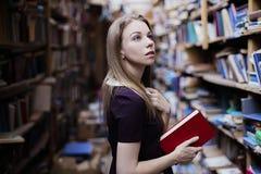 一个可爱的学生女孩的生活方式画象在葡萄酒图书馆或书店里 免版税库存图片
