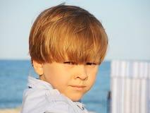 一个可爱的小男孩的画象海的背景的 免版税库存照片