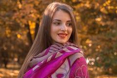 一个可爱的少妇的画象看对边并且微笑的一条桃红色围巾的在肩膀 免版税库存图片