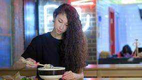 一个可爱的年轻亚裔女孩吃在一个亚洲咖啡馆的pho汤 采取与中国筷子的面条 ?? 影视素材