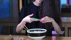 一个可爱的年轻亚裔女孩拍在智能手机pho汤的照片在一个亚洲咖啡馆 汉语,越南语或日语 影视素材