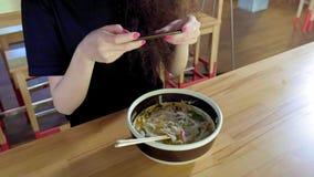 一个可爱的年轻亚裔女孩拍pho汤照片在一个亚洲咖啡馆的 汉语、越南或日本咖啡馆或者餐馆 股票录像