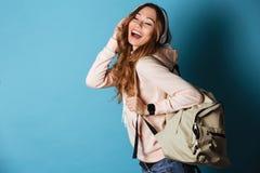 一个可爱的愉快的女学生的画象有背包的 免版税库存图片