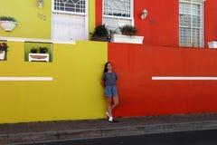 一个可爱的愉快的女孩拍照片对五颜六色的墙壁,在Bo Kaap处所街道,开普敦 免版税库存图片