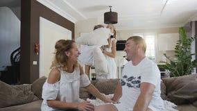 一个可爱的愉快的家庭 有她的丈夫的少妇坐长沙发并且获得乐趣谈话在他们后 股票录像