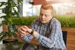 一个可爱的时髦的男性的一张水平的画象有红色头发和圆的面孔与穿戴的雀斑在控制中衬衣看 免版税库存照片