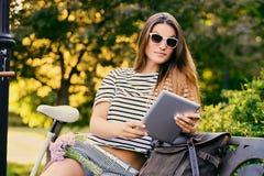 一个可爱的浅黑肤色的男人的画象坐与自行车的一条长凳 免版税图库摄影