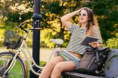 一个可爱的浅黑肤色的男人的画象坐与自行车的一条长凳 库存图片