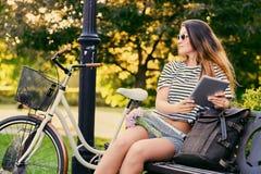 一个可爱的浅黑肤色的男人的画象坐与自行车的一条长凳 图库摄影