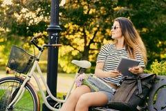 一个可爱的浅黑肤色的男人的画象坐与自行车的一条长凳 库存照片