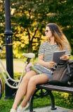 一个可爱的浅黑肤色的男人的画象坐与自行车的一条长凳 免版税库存图片