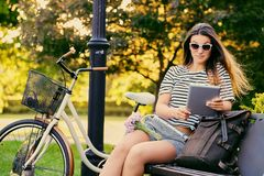 一个可爱的浅黑肤色的男人的画象坐与自行车的一条长凳 免版税库存照片