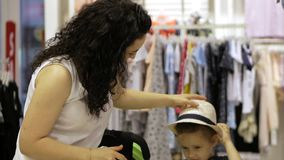 一个可爱的浅黑肤色的男人在商店采摘一个小女儿的一个帽子 有一个女儿的美丽的妇女在超级市场 A 股票录像