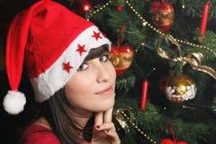 一个可爱的深色的女孩的纵向有圣诞节帽子的 免版税库存图片