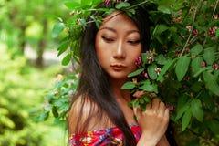 一个可爱的神奇亚裔女孩的画象有绿色叶子的 秀丽,化妆用品 免版税库存照片