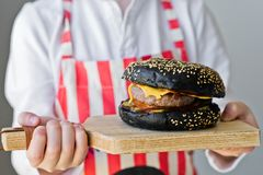 一个可爱的红发男孩拿着一块木砧板用汉堡包 烹调黑cheeseberger的食谱 库存图片