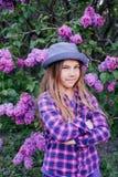 一个可爱的美丽的年轻式样女孩的照片五颜六色的衬衣的有长的头发的在夏天丁香庭院里 库存照片