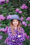 一个可爱的美丽的年轻式样女孩的照片五颜六色的衬衣的有长的头发的在夏天丁香庭院里 图库摄影