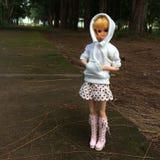 一个可爱的葡萄酒TAKARA玩偶单独站立在一条偏僻的路 她等待将通过并且接她的人 免版税库存图片