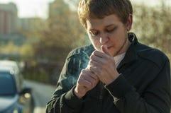 一个可爱的行家的画象有胡子的,抽香烟户外 免版税库存照片