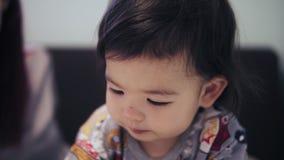一个可爱的逗人喜爱的亚裔小孩男孩吃着在他的年轻母亲旁边的曲奇饼有红色头发的 股票录像